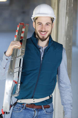 happy man in builder uniform smiling at the camera