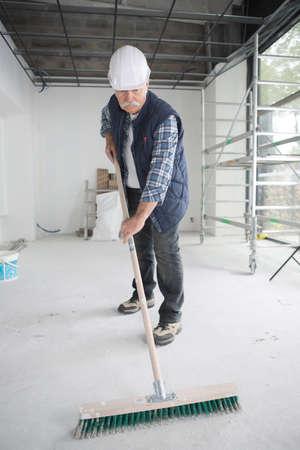 sweeping the floor of dust