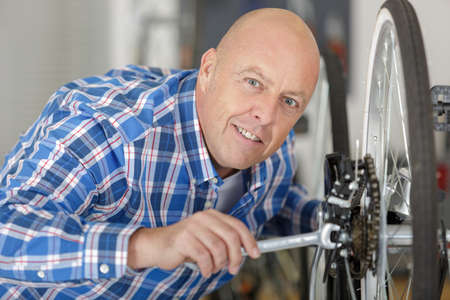 male smiling mechanic checking the tires on a bike