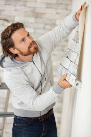 man holding wallpaper against a wall for visual effect