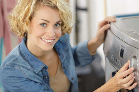 woman turning the dial on a washing machine