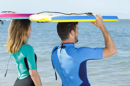couple in wetsuits walking to the sea bodyboards on heads 免版税图像