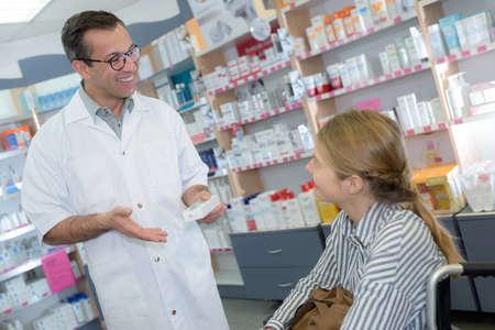 male chemist explaining product-details to customer in pharmacy 版權商用圖片