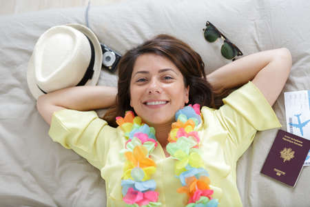 woman laying on bed before going on holidays