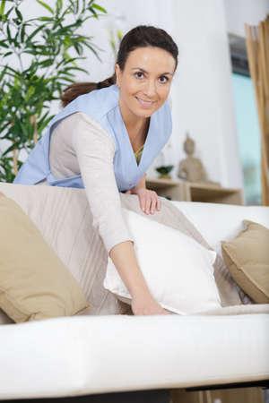 pretty adult woman cleaning sofa at home Zdjęcie Seryjne
