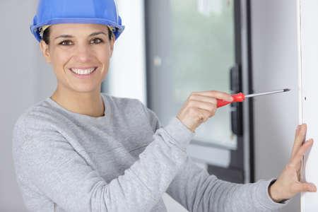 woman builder screwing a window frame