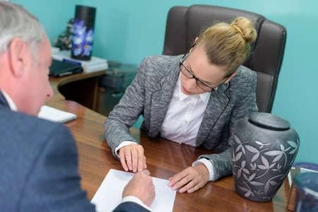 female undertaker asking client to sign paperwork urn on desk Foto de archivo