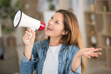happy carefree woman making megaphone announcement