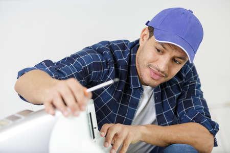 man using a screw driver in a machine