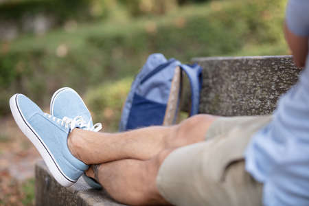 view male feet sitting on wooden bench
