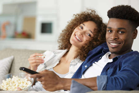 couple relaxing on the sofa eating popcorn and watching television Archivio Fotografico