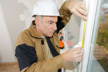 double glazing installer measuring the window