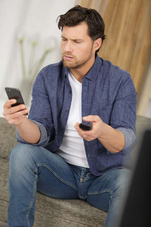 man holding smartphone and using an app with remote control