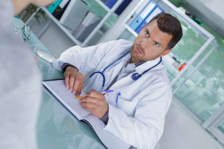 doctor with patient finding date in diary for appointment