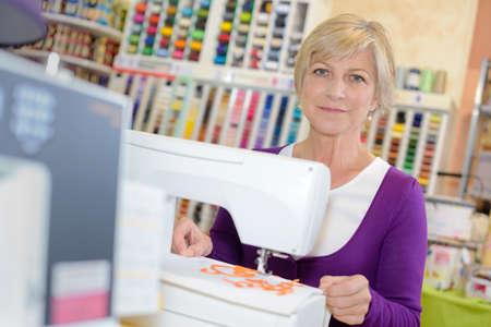 smiley woman sewing on sewing-machine 版權商用圖片