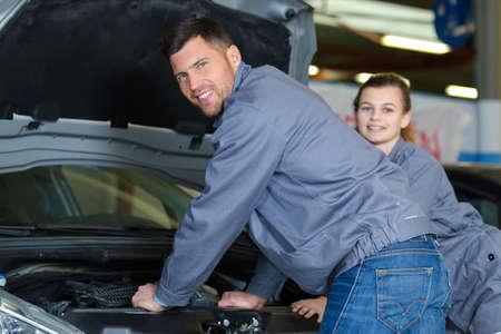 two apprentice mechanics looking to camera beside a car Archivio Fotografico