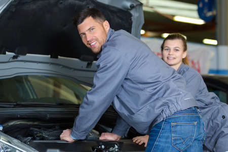 two apprentice mechanics looking to camera beside a car Stock Photo