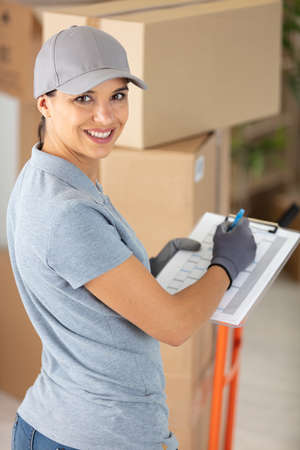 female courier delivering packages holding clipboard