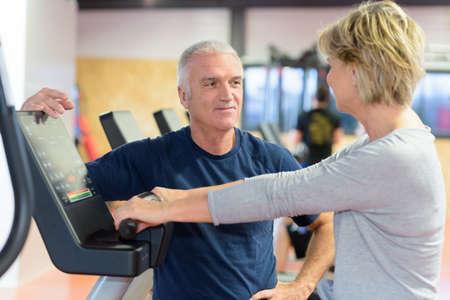 happy senior couple using trainer bike in a gym