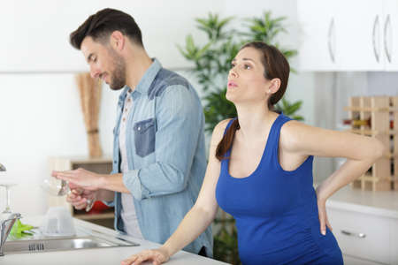 pregnant wife with back ache and husband in the kitchen