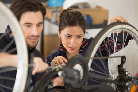 man and woman repair bicycle together Stock Photo