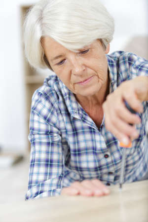 senior woman with screwdriver fixing something at home