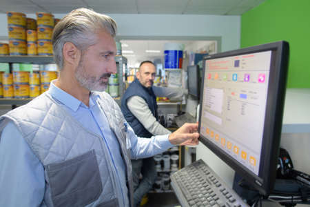 factory technician checking data on the screen