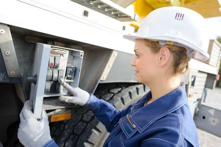 Woman operating controls on side of crane