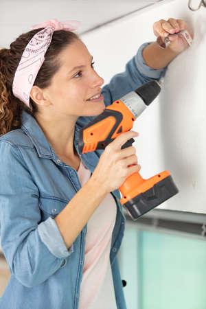 woman installing bracket for curtain rail