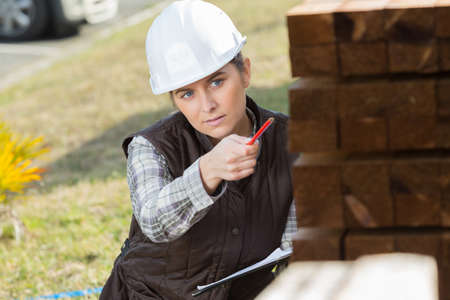 woman holding lumber inspection outdoors