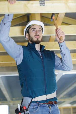 roofer builder working on roof structure