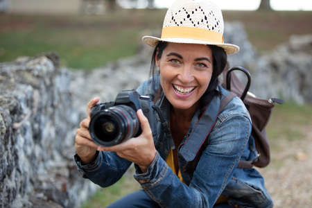 smiling female photographer crouching to take a picture