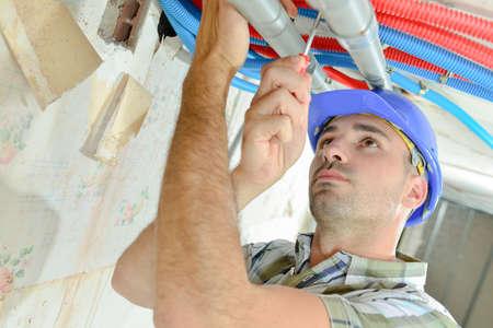 a builder is srewing pipe