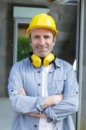 happy mature builder outdoors in hardthat looking at camera