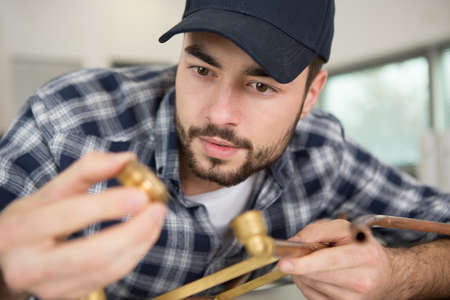 male worker finding correct copper pipe fittings