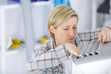 blonde handywoman cleaning fixing ventilation system Фото со стока