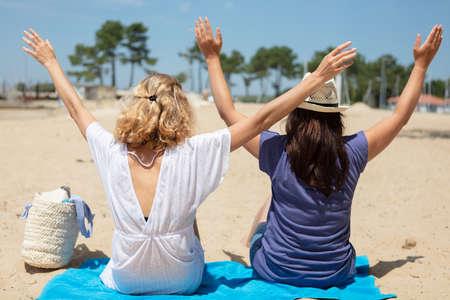 two women on the beach holding their hands up Standard-Bild
