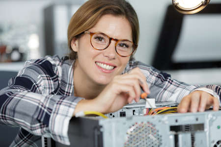 woman repairing computer with screwdriver