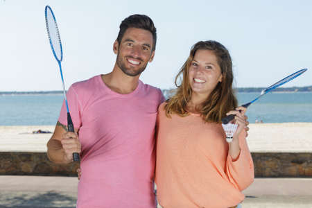 young couple playing badminton next to the beach