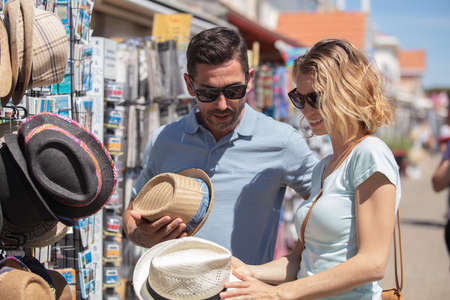 couple at outdoor summer market looking at hats