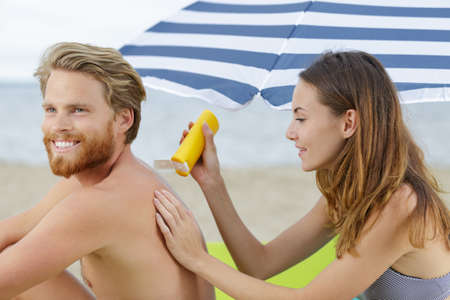 woman is applying sunscreen on the back of a man