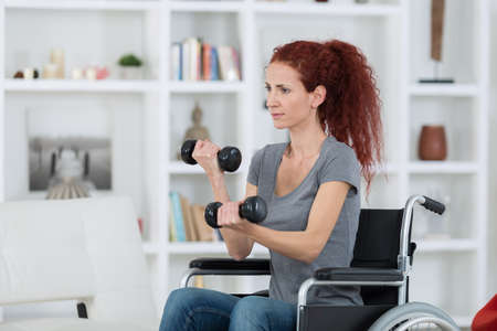 woman sitting in wheelchair working out with dumbbells Stockfoto