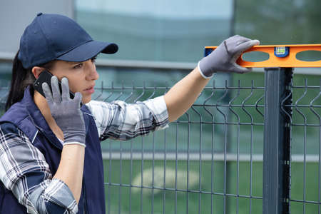 female worker checking fence with spirit level while using smartphone