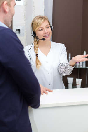 young female receptionist talking to client Imagens