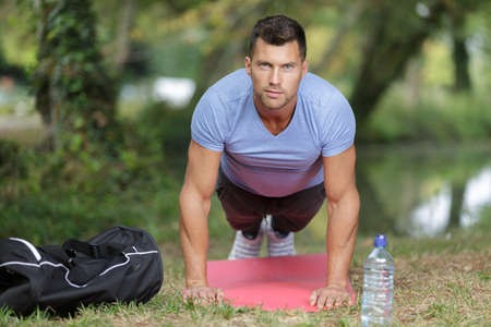 muscular young guy doing push-ups in park on lawn