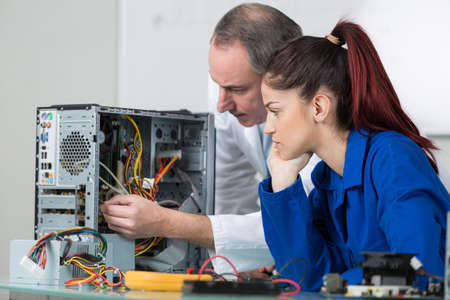 Trainee technician learning to repair computer