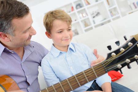 Man holding guitar, child sat on his lap 版權商用圖片