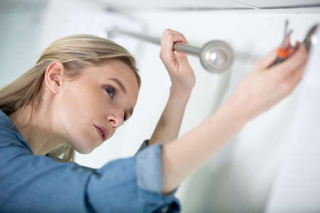 woman fits a bracket for mounting a curtain rail Stock fotó