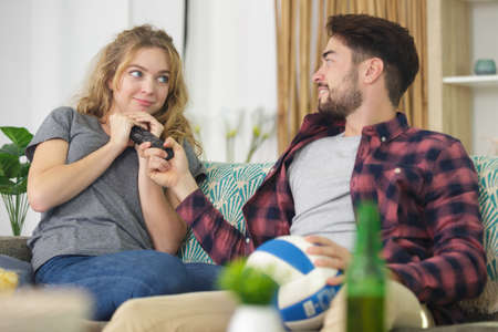 smiling young couple sharing joysticks on sofa at home