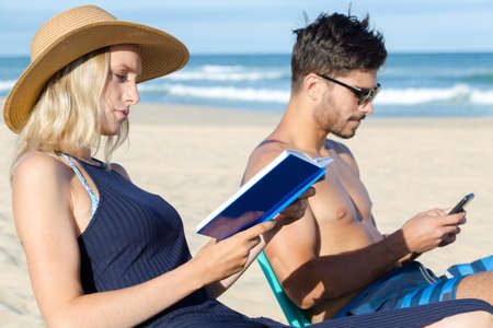 couple on holidays reading and using the phone Standard-Bild